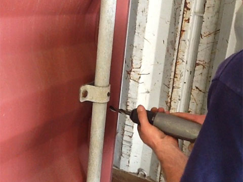 Drilling holes in a shipping container